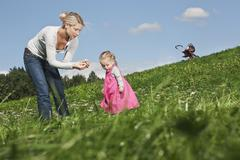 Germany, Cologne, Mother showing flower to her daughter (2-3 Years) - stock photo
