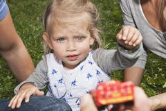 Germany, Cologne, Girl (2-3 Years) looking at toy with parents Stock Photos
