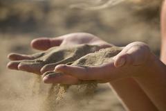 Italy, Jesolo, Teenage girl playing with sand on beach Stock Photos
