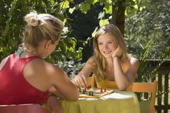 Austria, Salzburger Land, Teenage girls (14-15) playing ludo in garden - stock photo