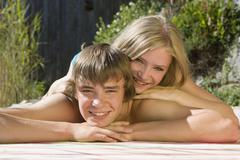 Stock Photo of Austria, Salzburger Land, Teenagers (14-15) lying in garden, smiling, portrait