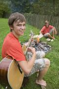 Austria, Salzburger Land, Teenage boys (14-15) in garden, sitting at campfire - stock photo