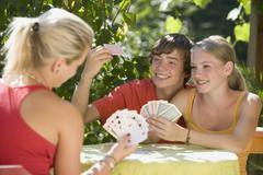 Stock Photo of Austria, Salzburger Land, Teenagers (14-15) playing cards in garden