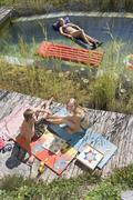 Austria, Salzburger Land, Teenagers (14-15) relaxing at garden pool, elevated - stock photo