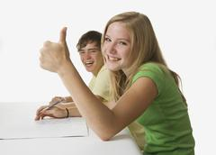 Stock Photo of Girl and boy looking at camera, smiling, close up.