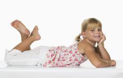 Girl (4-5) with feet up lying on white background, smiling, portrait Stock Photos