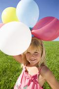Stock Photo of Austria, Mondsee, Girl (4-5) standing in meadow holding balloons, smiling,