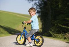 Austria, Mondsee, Boy (2-3) riding bicycle, smiling, portrait Stock Photos