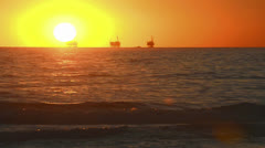 Winter sunset over the Pacific Ocean behind three oil platforms off of the Stock Footage