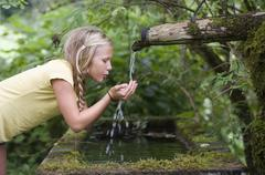 Austria, Mondsee, Girl (12-13 Years) drinking water from water spout - stock photo
