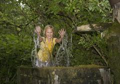 Austria, Mondsee, Girl (12-13 Years) playing with water in water trough - stock photo