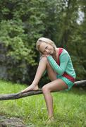 Stock Photo of Austria, Mondsee, Girl (12-13 Years) sitting on branch, portrait