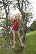 Austria, Mondsee, Girl (12-13 Years) on a tree, portrait Stock Photos