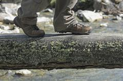 Lungau, Austria, Hiker walking on log above creek Stock Photos