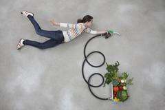 Mid adult woman holding industrial hose connected to vegetable box Stock Photos