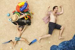 Stock Photo of Germany, Father and son with toys and baggage at beach