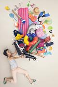 Stock Photo of Germany, Artificial scene with woman opening baggage full of beach toys