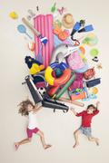 Stock Photo of Germany, Artificial scene with children opening baggage full of beach toys