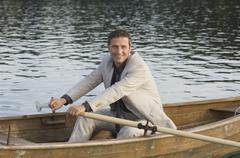 Germany, Bavaria, Wesslinger See, Business man rowing boat in lake after work Stock Photos