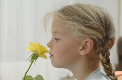 Germany, Bavaria, Girl smelling yellow rose - stock photo