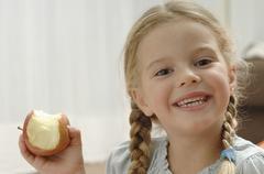 Germany, Bavaria, Girl holding apple, portrait, smiling - stock photo