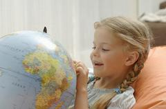 Germany, Bavaria, Girl looking at globe, close up Stock Photos