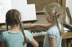 Germany, Bavaria, Two girls using piano and making music Stock Photos