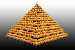 Stack of oranges in pyramid shape against grey background - stock photo