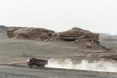 a heavy truck passing yardang landform in dunhuang, gansu of china - stock photo