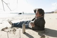 Germany, Hamburg, Man lying on sand with coffee flask near elbe riverside - stock photo