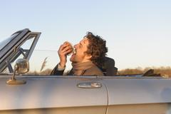 Stock Photo of Germany, Hamburg, Man eating fish sandwich in classic cabriolet car