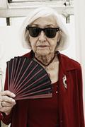 Germany, Bavaria, Munich, Senior woman with folding fan, portrait - stock photo