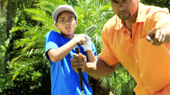 African American Father Enjoying Teaching Son Play Golf - stock footage