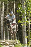 Germany, Bavaria, Chiemgau, Samerberg, Man doing stunt with mountain bike - stock photo