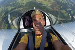 Germany, Bavaria, Bad Toelz, Mature man in glider, smiling, portrait Stock Photos