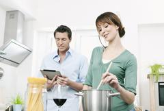 Man and woman preparing noodles in kitchen Stock Photos