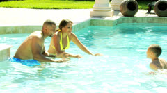 African American Parents Teaching Son Swimming Pool - stock footage