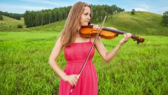Violinist plays on a green meadow Stock Footage