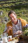 Stock Photo of Austria, Salzburg Country, Filzmoos, Man having his snacks, smiling, portrait