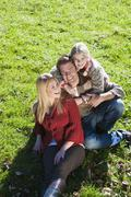 Austria, Flachau, Salzburg, Family sitting on autumn meadow - stock photo