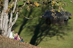 Austria, Salzburg, Flachau, Family sitting in autumn meadow - stock photo
