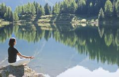 Austria, Styria, Mid adult woman meditating at lake duisitzkar in schladming - stock photo