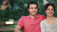 Stock Video Footage of Caucasian couple lovers sitting on a park bench happy