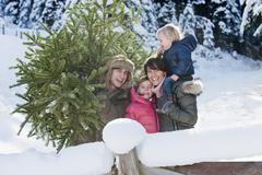 Austria, Salzburg Country, Flachau, View of family with christmas tree in snow Stock Photos