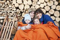 Austria, Salzburg Country, Flachau, Family under woollen blanket sitting in Stock Photos