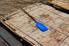 a blue oar on a bamboo raft on kwainoi river with wild landscape in kanchanab - stock photo