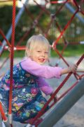 Germany, Munich, Girl climbing on climbing frame in playground, smiling, Stock Photos