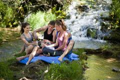Stock Photo of Italy, Tuscany, Friends with champagne sitting on grass and having picnic