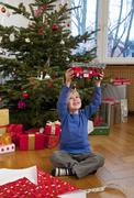 Germany, Munich, Boy sitting christmas present holding toy fire engine Stock Photos