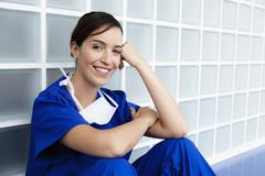 Young doctor wearing scrubs and sitting in corridor, smiling, portrait - stock photo